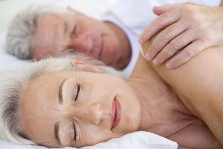 Couple lying in bed together sleeping