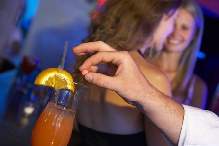 Man Drugging Woman's Drink In Bar