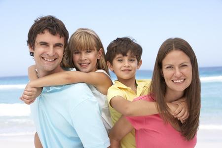 Family Having Piggyback Fun On Beach Holiday