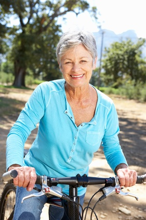 Photo pour Senior woman on country bike ride - image libre de droit