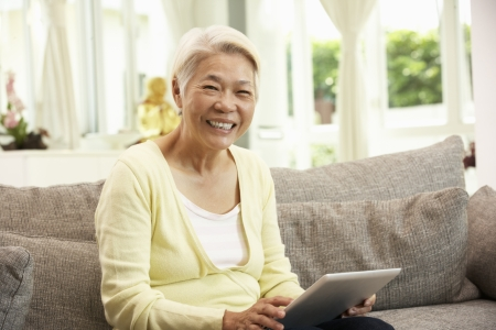 Photo for Senior Chinese Woman With Tablet Computer Whilst Relaxing On Sofa At Home - Royalty Free Image