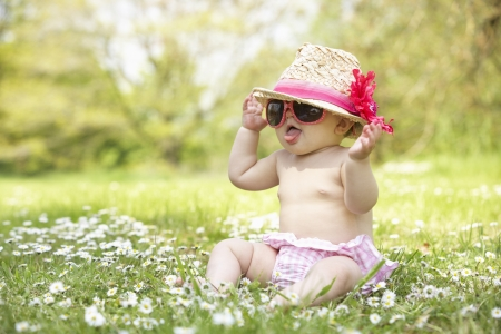 Photo for Baby Girl In Summer Dress Sitting In Field Wearing Sunglasses And Straw Hat - Royalty Free Image