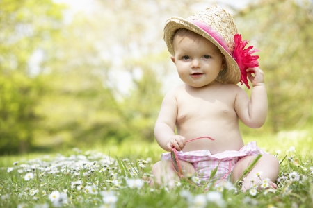 Photo pour Baby Girl In Summer Dress Sitting In Field Wearing Sunglasses And Straw Hat - image libre de droit