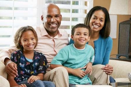 Photo pour Portrait Of Family Sitting On Sofa Together - image libre de droit