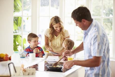 Photo pour Father Preparing Family Breakfast In Kitchen - image libre de droit