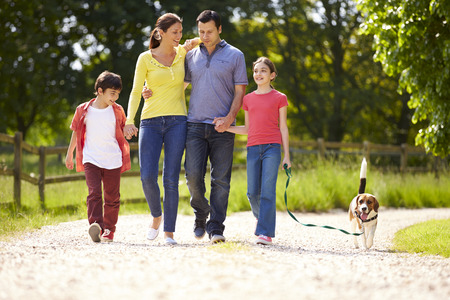 Foto de Hispanic Family Taking Dog For Walk In Countryside - Imagen libre de derechos