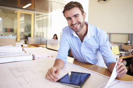 Photo for Male Architect With Digital Tablet Studying Plans In Office - Royalty Free Image