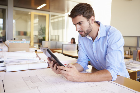 Foto de Male Architect With Digital Tablet Studying Plans In Office - Imagen libre de derechos