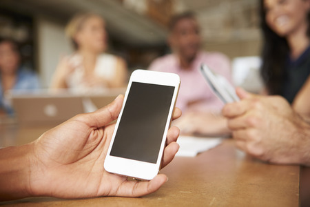 Mobile Phone Being Used By Architect In Meeting