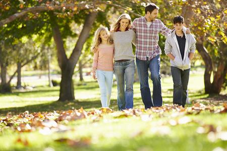 Foto de Family Walking Through Autumn Woodland - Imagen libre de derechos