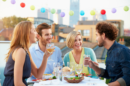 Photo for Group Of Friends Eating Meal On Rooftop Terrace - Royalty Free Image