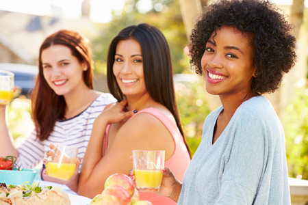 Three Female Friends Enjoying Meal At Outdoor Party