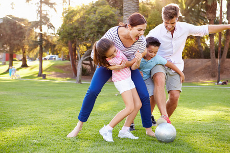 Foto de Family Playing Soccer In Park Together - Imagen libre de derechos