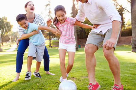 Photo for Family Playing Soccer In Park Together - Royalty Free Image