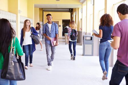 Photo pour Group Of High School Students Walking Along Hallway - image libre de droit