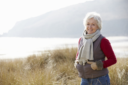 Photo for Senior Woman Walking Through Sand Dunes On Winter Beach - Royalty Free Image