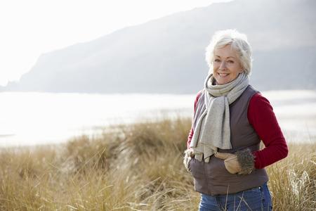Photo pour Senior Woman Walking Through Sand Dunes On Winter Beach - image libre de droit