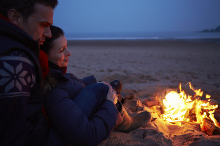 Photo for Couple Sitting By Fire On Winter Beach - Royalty Free Image