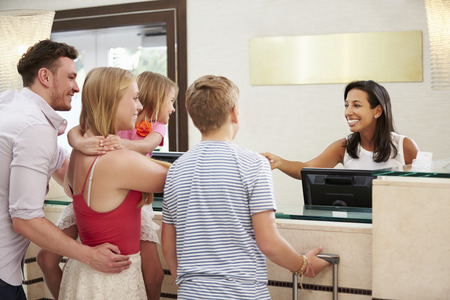 Photo for Family Checking In At Hotel Reception - Royalty Free Image