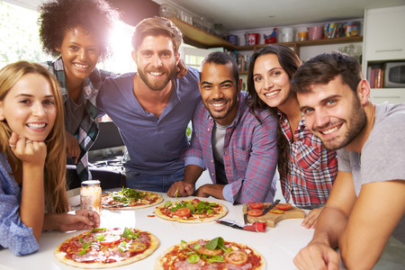 Photo for Group Of Friends Making Pizza In Kitchen Together - Royalty Free Image