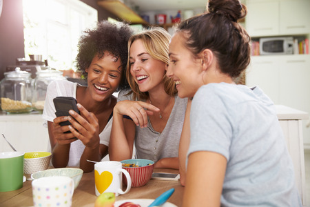 Photo for Female Friends Eating Breakfast Whilst Checking Mobile Phone - Royalty Free Image