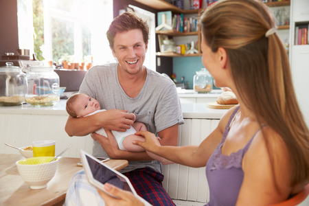 Photo for Family With Baby Girl Use Digital Tablet At Breakfast Table - Royalty Free Image