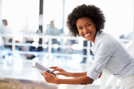 Foto de Portrait of smiling woman in office with tablet - Imagen libre de derechos