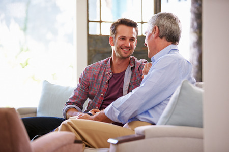 Photo for Senior Father With Adult Son Relaxing On Sofa At Home - Royalty Free Image