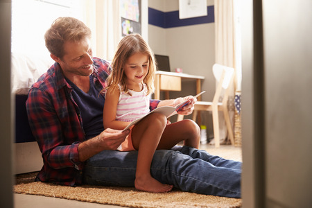 Photo for Father and young daughter reading together - Royalty Free Image