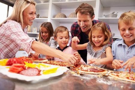 Photo pour Family making pizza for dinner - image libre de droit