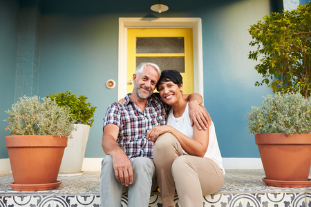 Photo for Mature Couple Sitting On Steps Outside House - Royalty Free Image