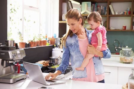 Photo for Mother With Young Daughter Using Laptop In Kitchen - Royalty Free Image