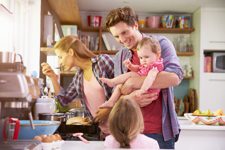 Photo for Family Cooking Meal In Kitchen Together - Royalty Free Image