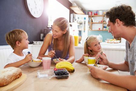 Photo pour Family Eating Breakfast At Kitchen Table - image libre de droit