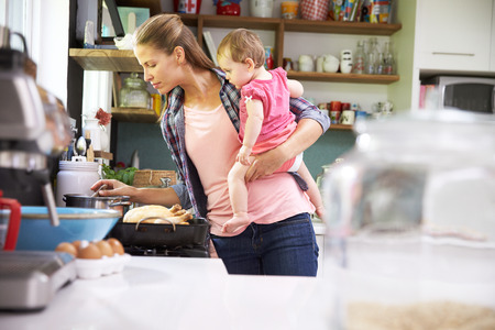 Photo for Mother Cooking Meal Whilst Holding Daughter In Kitchen - Royalty Free Image