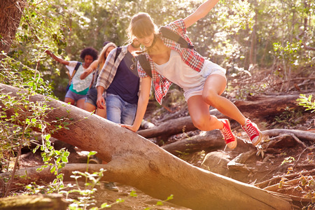 Photo for Group Of Friends Jumping Over Tree Trunk On Countryside Walk - Royalty Free Image