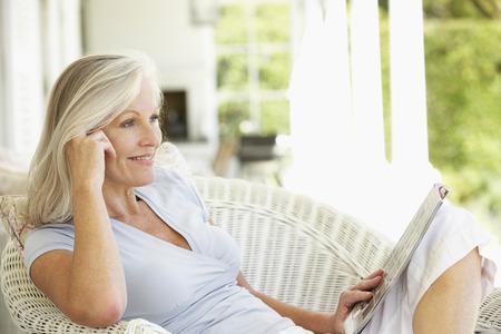 Photo pour Senior woman reading outside - image libre de droit