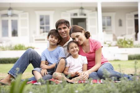 Photo pour Family Sitting Outside House On Lawn - image libre de droit