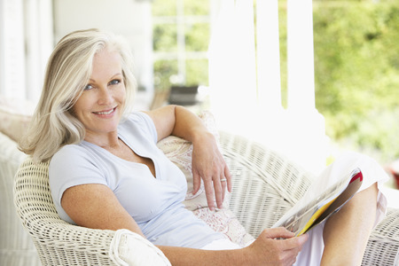 Foto per Senior Woman Sitting Outside Reading Magazine - Immagine Royalty Free