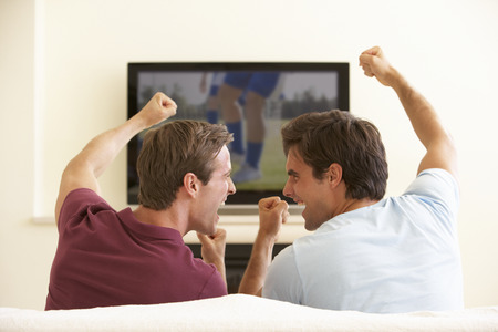 Photo for Two Men Watching Widescreen TV At Home - Royalty Free Image