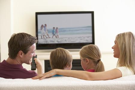 Photo pour Family Watching Widescreen TV At Home - image libre de droit