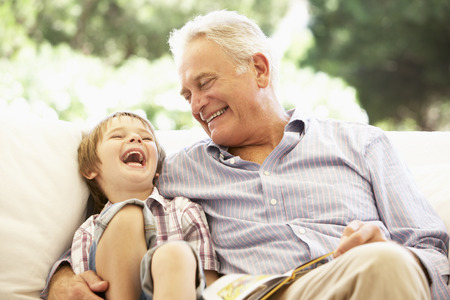 Photo for Grandfather With Grandson Reading Together On Sofa - Royalty Free Image