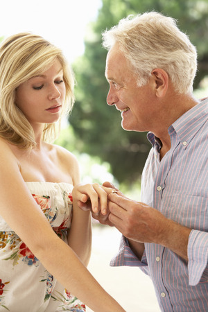 Foto per Older Man Proposing To Younger Woman - Immagine Royalty Free