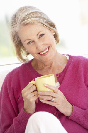 Photo for Senior Woman Relaxing At Home With Hot Drink - Royalty Free Image