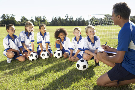 Group Of Children In Soccer Team Having Training With Coach