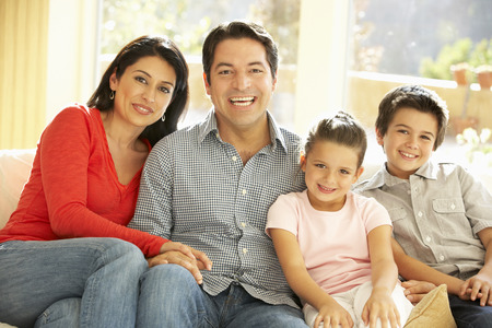 Photo for Young Hispanic Family Relaxing On Sofa At Home - Royalty Free Image