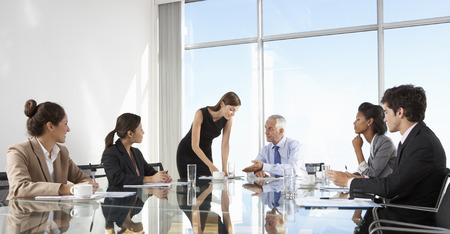 Foto de Group Of Business People Having Board Meeting Around Glass Table - Imagen libre de derechos