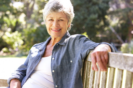 Photo for Senior Woman Relaxing On Park Bench - Royalty Free Image