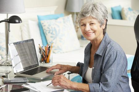Photo pour Senior Woman Working In Home Office - image libre de droit