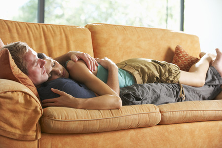 Photo for Romantic Couple Lying On Sofa At Home - Royalty Free Image